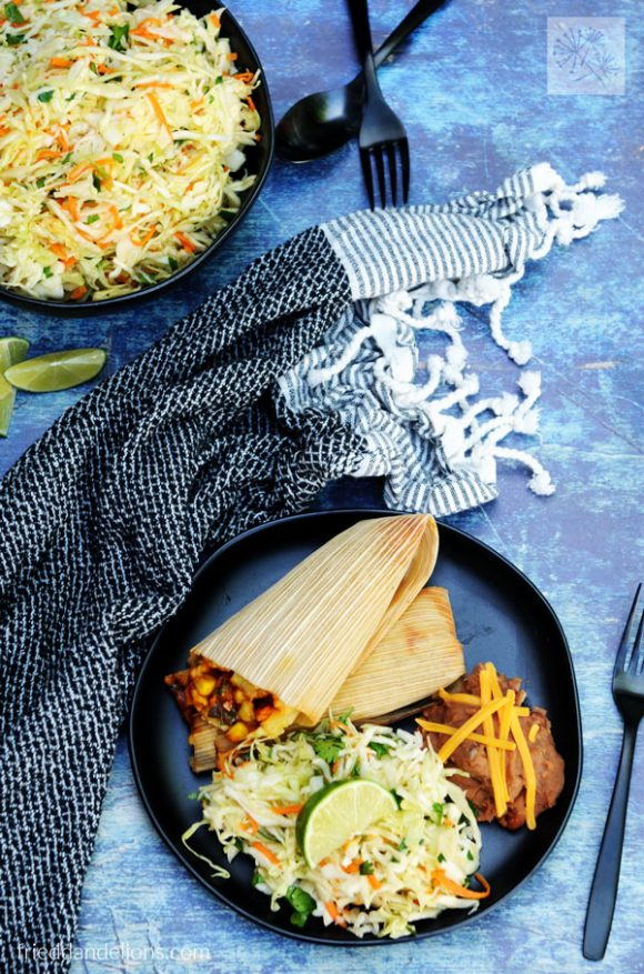 overhead view of plate with cabbage slaw, tamales, beans, black napkin, black silverware, blue background