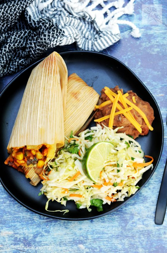 black plate filled with cabbage slaw, refried beans, tamales, with blue background and black napkin