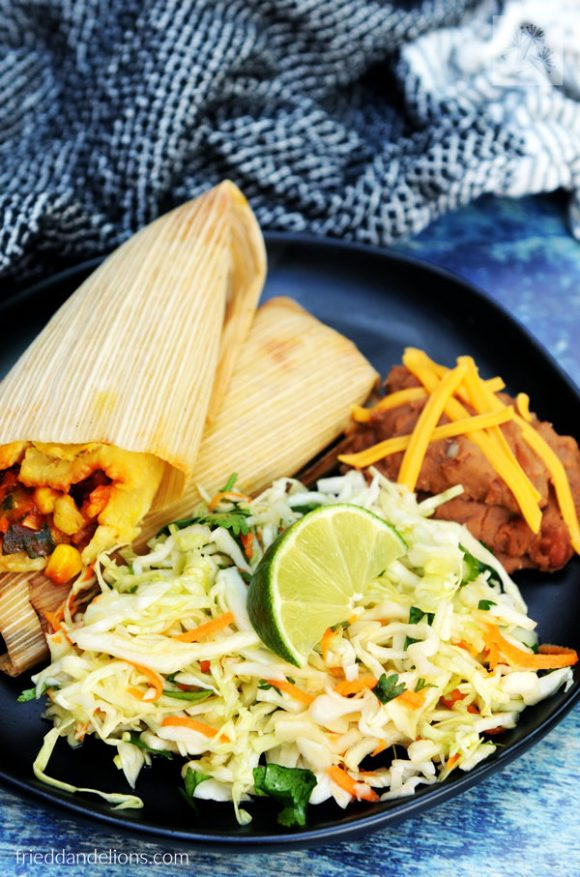 close up of plate of cabbage slaw, tamales, beans, with black napkin and blue background