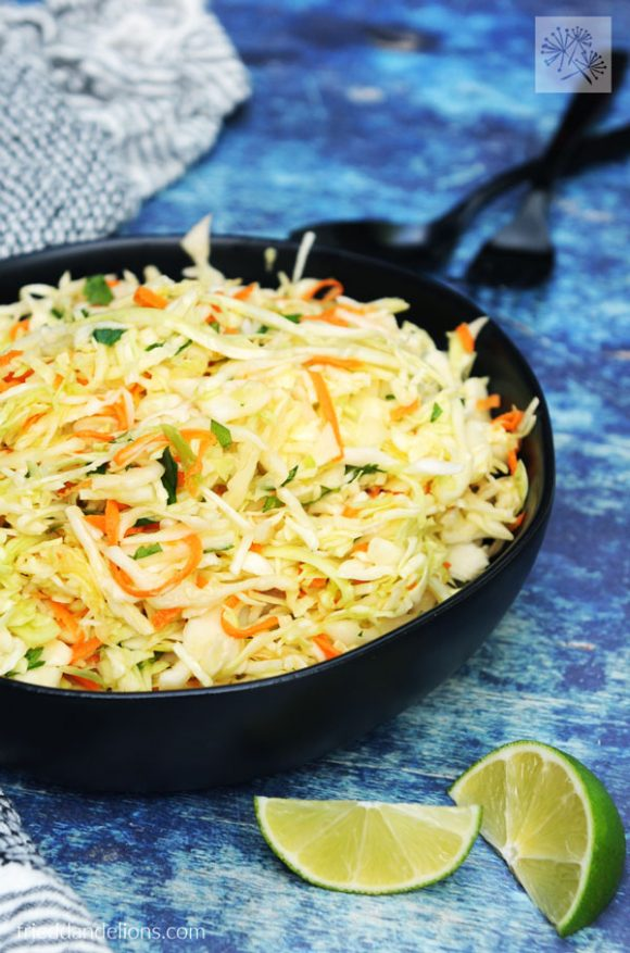 close up of large bowl of cabbage slaw with lime wedges, blue background, black silverware