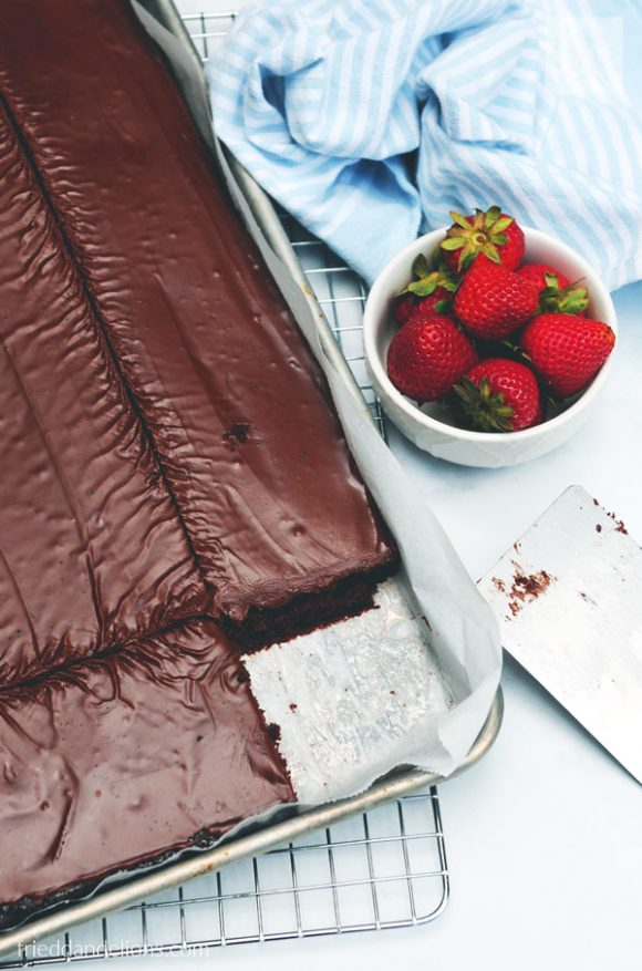 overview of sheet pan of vegan Texas Sheet Cake with bowl of strawberries and cake server