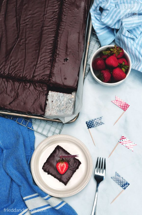 overhead view of sheet pan vegan Texas Sheet Cake with slice on a plate, flag decorations, and bowl of strawberries