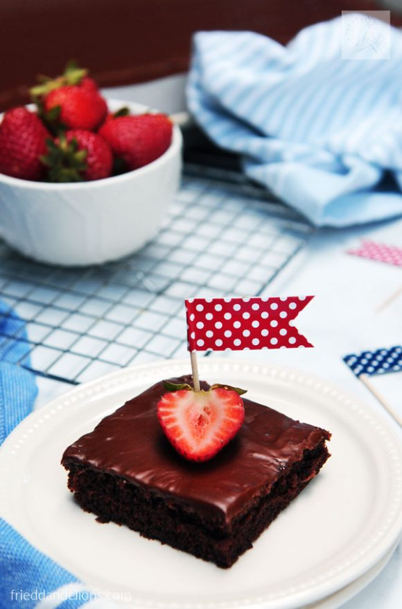 slice of vegan Texas Sheet Cake with strawberry and flag on top, bowl of strawberries and blue napkin in the background