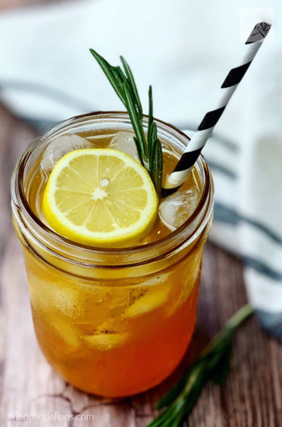 close up of jar of Rosemary Lemon Iced Tea with lemon and rosemary garnish and black and white striped straw