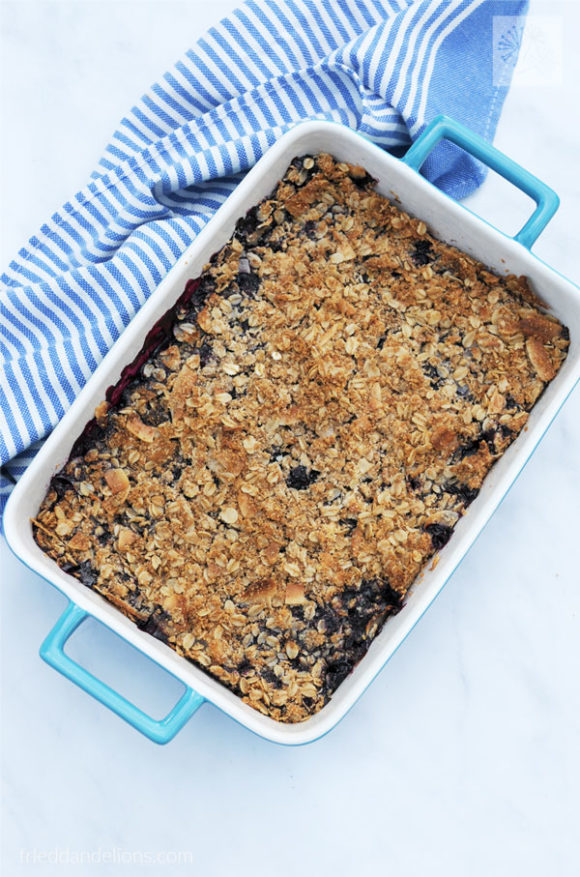 overhead shot of vegan blueberry crisp in a blue baking dish with blue and white striped napkin in the background on a white marble counter