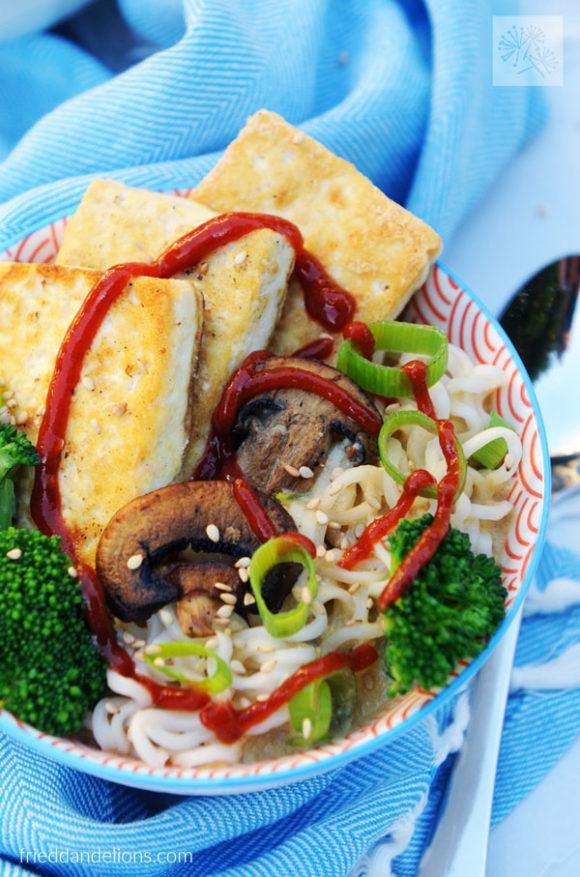 close up of bowl of vegan creamy sesame ramen drizzled with sriracha
