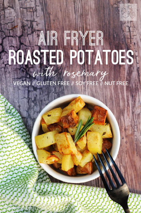 overhead shot of air fryer roasted potatoes with wood slab background, green napkin, black fork, and text overlay