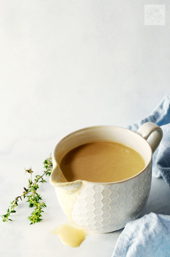 gravy boat filled with dairy free onion gravy with a blue napkin, sprig of thyme in background
