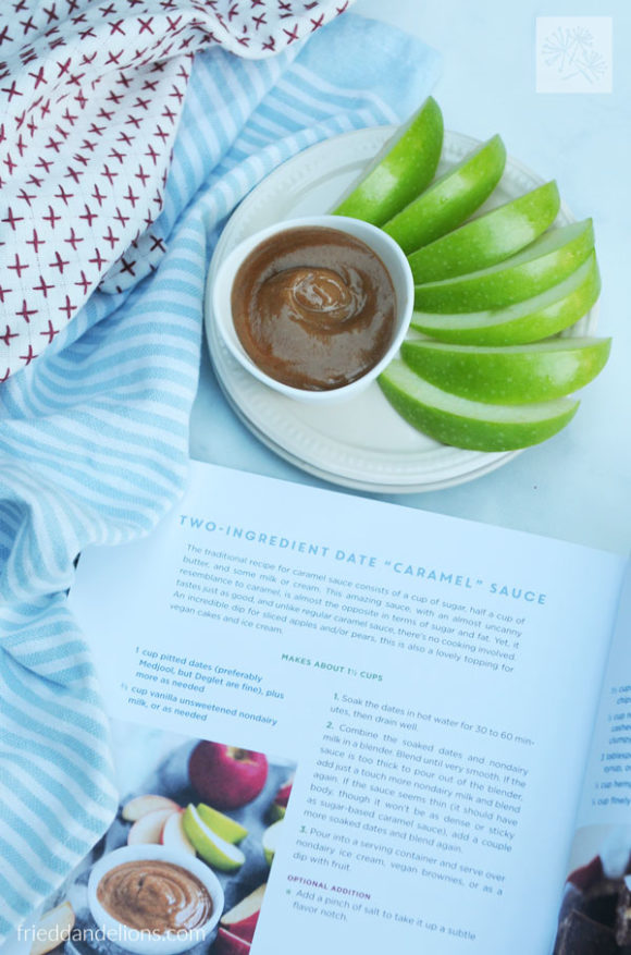 bowl of date caramel with granny smith apples, with 5-Ingredient Vegan cookbook open to Two Ingredient Date Caramel Sauce recipe