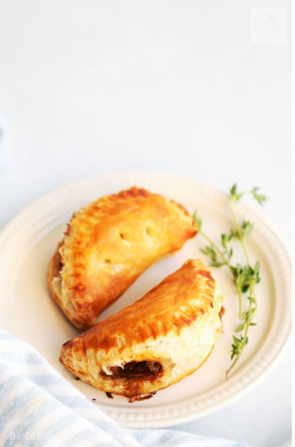 French onion puff pastry cups formed into empanadas with sprig of thyme on white plate with blue striped napkin
