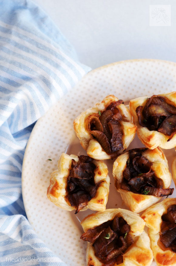 close up of French onion puff pastry cups on white plate with blue striped napkin