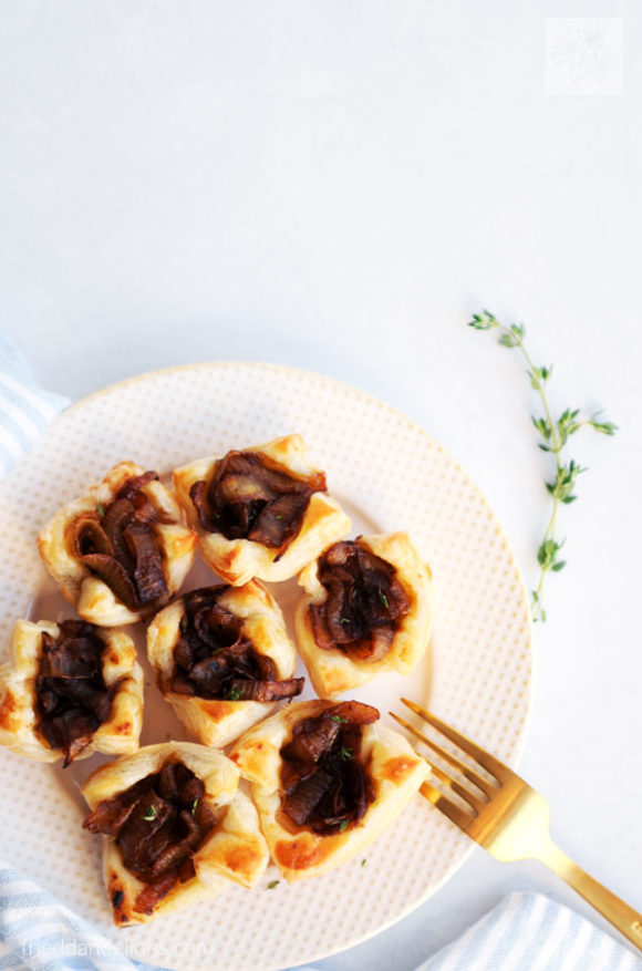 white plate of French onion puff pastry cups with gold fork, sprig of thyme, blue striped napkin