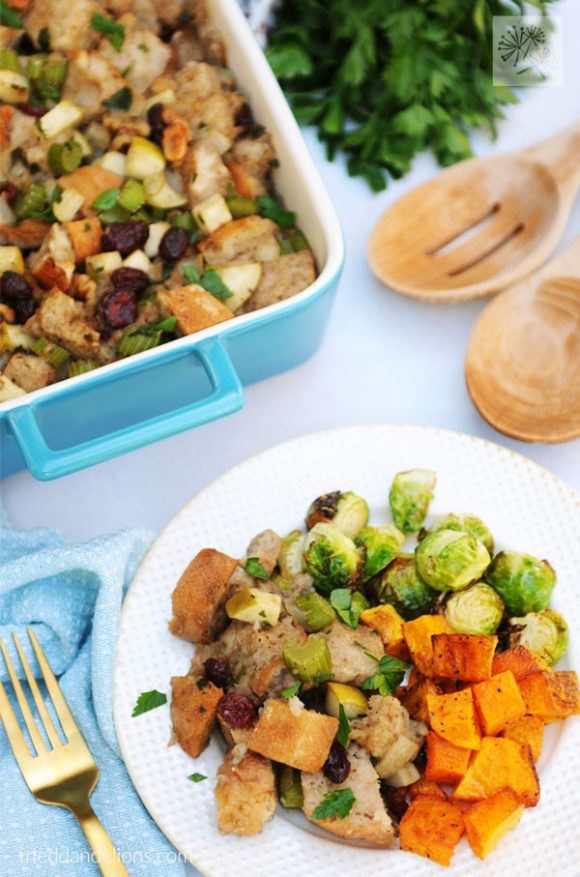 overhead view of plate of Traditional Vegan Stuffing with baking dish in background, parsley, and wooden spoons