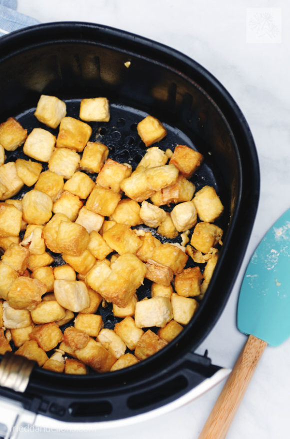 air fryer basket filled with crispy air fried tofu with aqua spatula in background