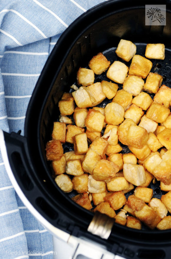 air fryer basket filled with crispy air fried tofu with blue striped napkin in the background