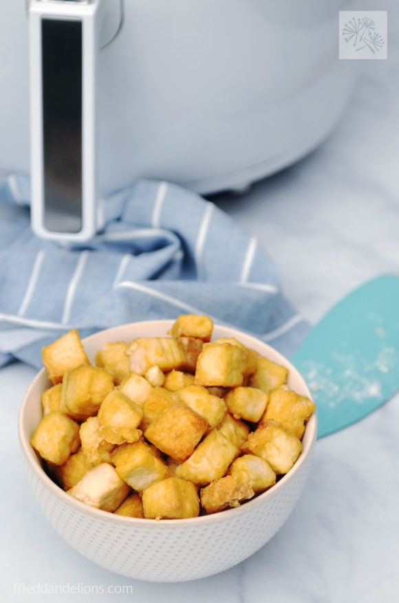 bowl of crispy air fried tofu in front of air fryer with aqua spatula
