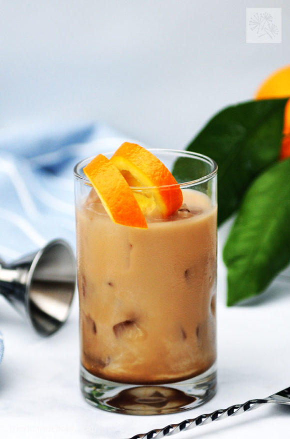 close up of glass of vegan white Russian with orange garnish and orange leaves in the background