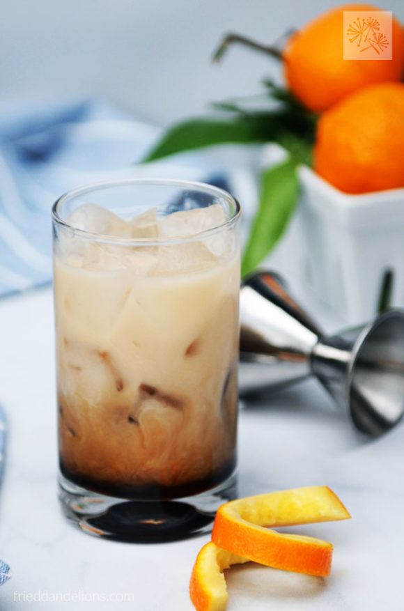 creamer mixing into vegan white Russian with orange garnish in foreground and basket of oranges in the background