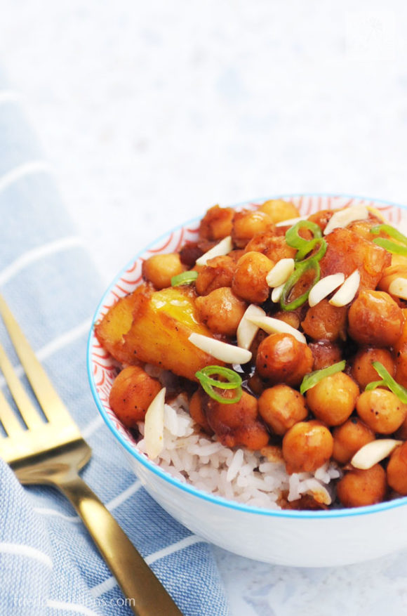 bowl of stir fried chickpeas with pineapples, blue napkin, and gold fork