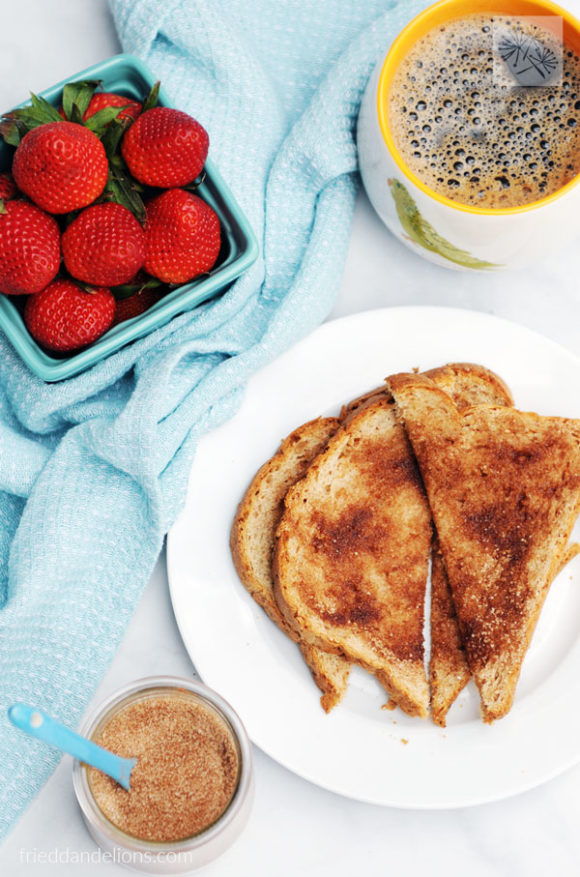 jar of cinnamon sugar toast topping with slices of toast, strawberries, and a mug of coffee