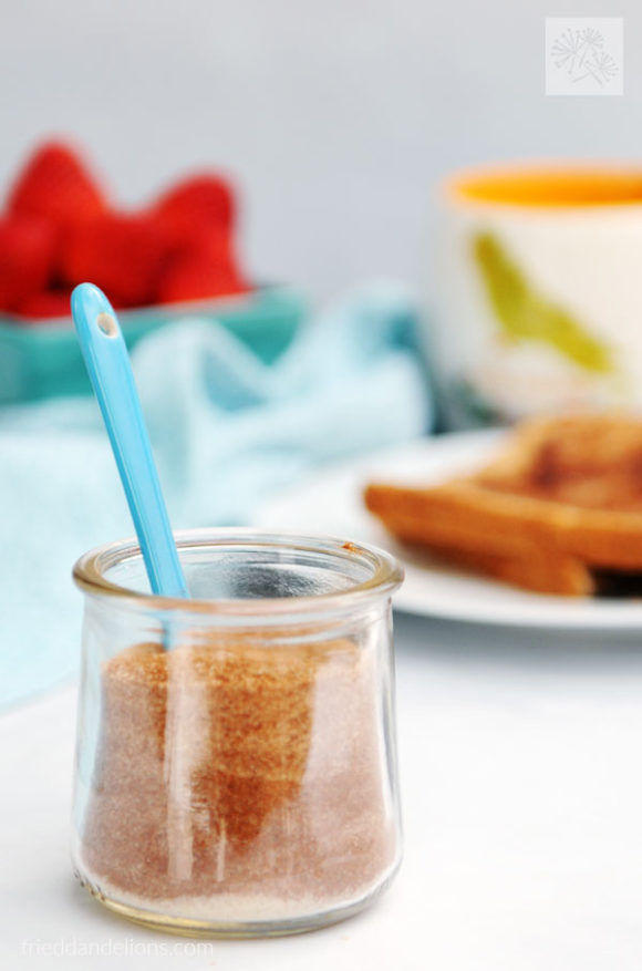 jar of cinnamon sugar toast topping with blue spoon