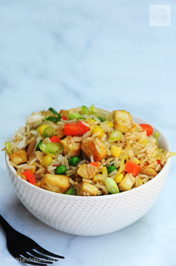 white bowl of Vegan Cabbage Fried Rice with black fork