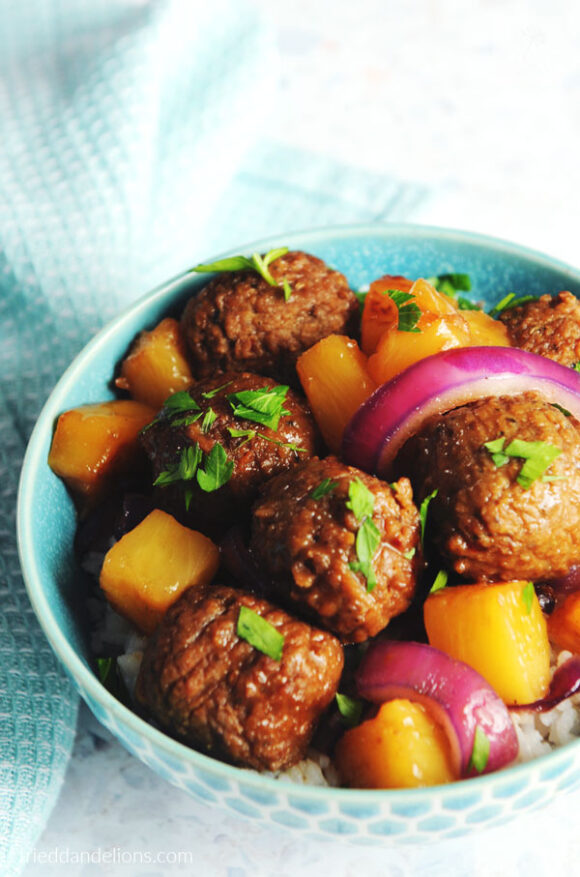 blue bowl of vegan waikiki meatballs with blue dishtowel in background