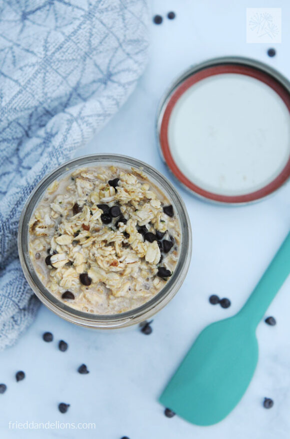 overhead view of chocolate chip cookie overnight oats with aqua spatula and chocolate chips