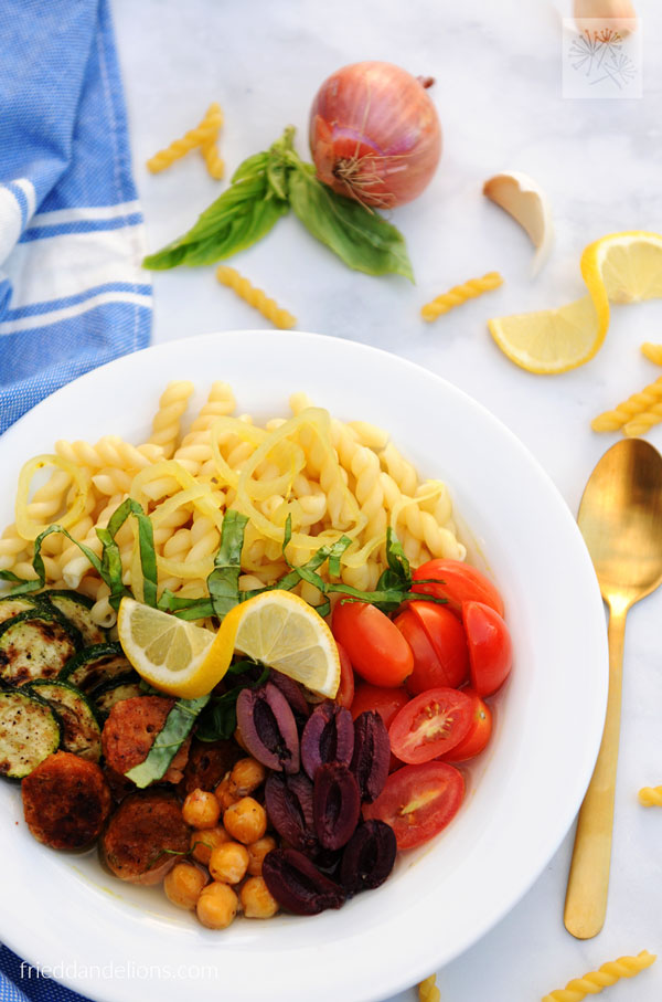 pasta power bowl with pasta, tomatoes, olives, chickpeas, sausage, zucchini, and lemon with blue napkin and gold spoon