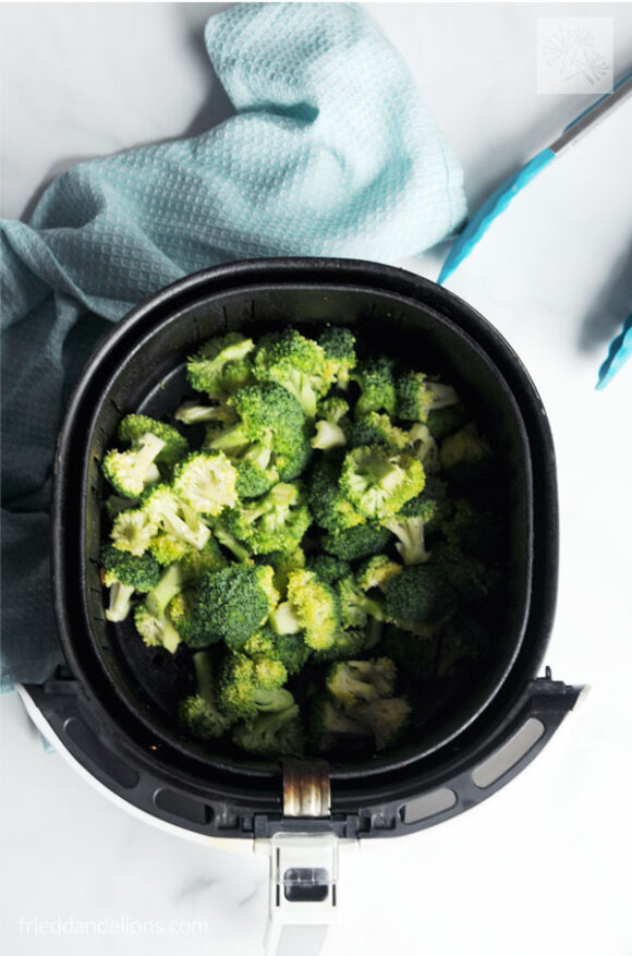overhead of air fried broccoli in the basket with blue napkin and blue tongs