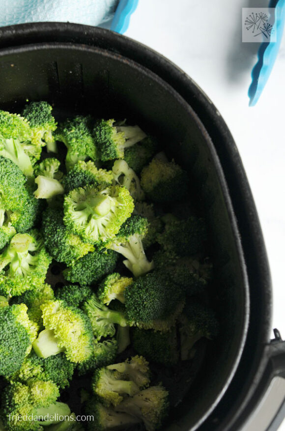 overhead shot of air fryer basket with air fried broccoli