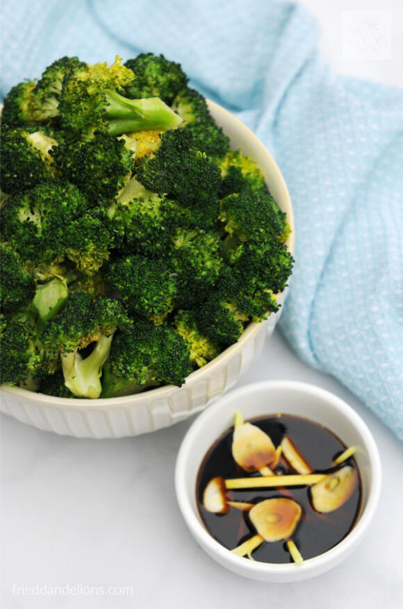 overhead of bowl of air fried broccoli with Din Tai Fung dipping sauce