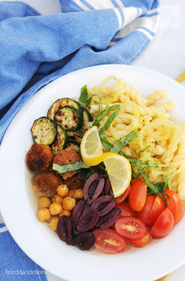 pasta power bowl with pasta, tomatoes, olives, chickpeas, sausage, zucchini, and lemon with blue napkin