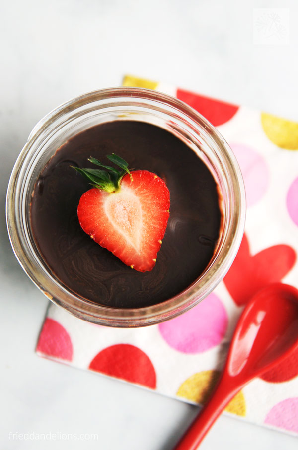 overhead view of vegan vanilla pudding cup with strawberry garnish, red spoon, and napkin with red heart
