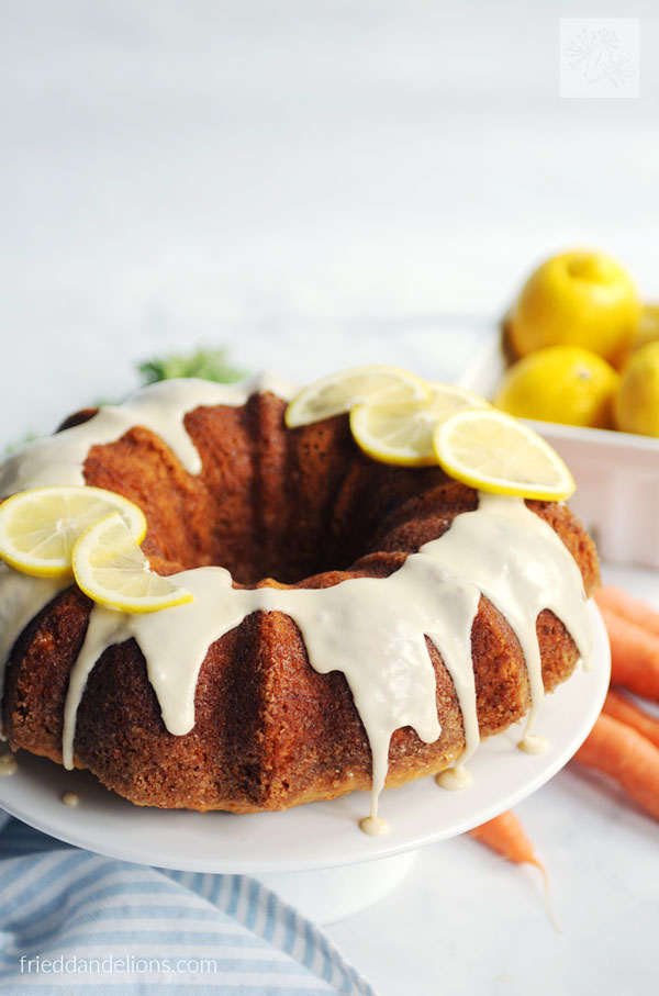 carrot cake with lemon glaze with bowl of lemons in the background