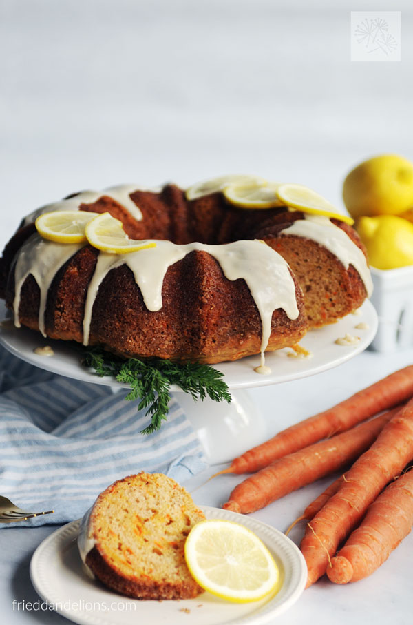 carrot cake with lemon glaze with a slice in the foreground, carrots, and lemons in the background, and a blue and white striped napkin